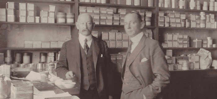 Aged photograph of gentlemen standing in front of tea stock in a shop.